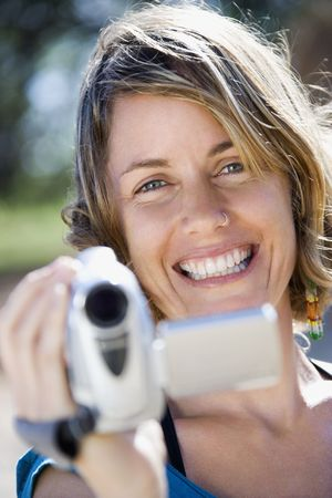 Mid-adult Caucasian woman outdoors pointing video camera at viewer.