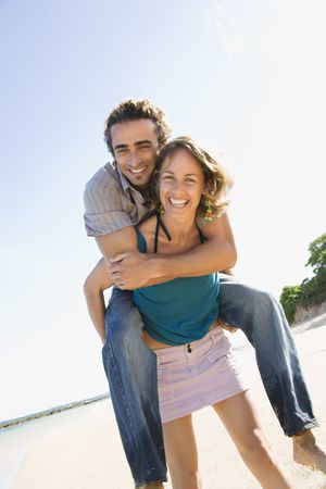 piggyback ride: Mid-adult Caucasian woman giving man piggyback ride on beach.  Stock Photo