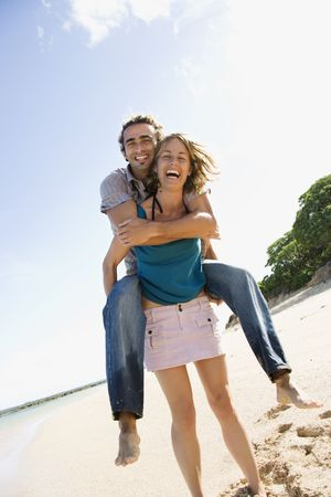 Mid-adult Caucasian woman giving man piggyback ride on beach.  Stock Photo