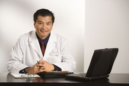 doctor office: Asian American male doctor sitting at desk with charts and laptop computer looking at viewer.