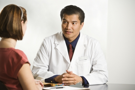 asian doctor: Asian American male doctor consulting with Caucasian female patient.