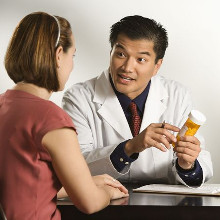 consultation woman: Asian American male doctor explaining medication to Caucasian female patient.