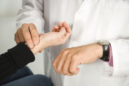 taking pulse: Doctor taking patients pulse.