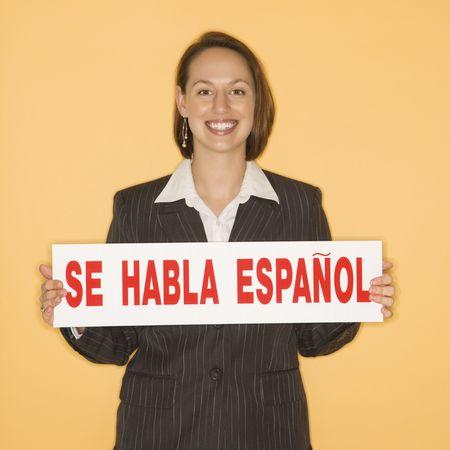 se: Caucasian businesswoman smiling holding sign reading se habla espanol.