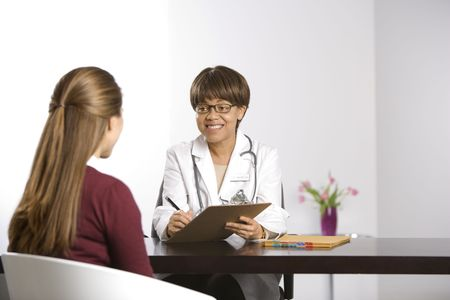 African American middle-aged female doctor sitting at desk talking to Caucasian mid-adult female patient taking notes on clipboard. Stock Photo - 2191336