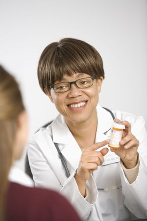 African American middle-aged female doctor sitting at desk explaining medication to Caucasian mid-adult female patient. Stock Photo - 2191184
