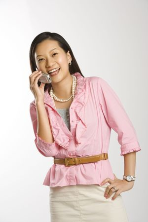 Portrait of Asian Chinese mid-adult female with hand on hip smiling and talking on cell phone. photo