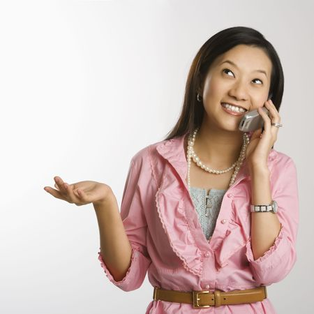 Portrait of Asian Chinese mid-adult female with hand out, looking up, smiling and talking on cell phone.