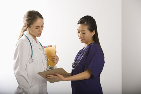 health facility: Caucasian mid-adult female doctor and Asian Chinese mid-adult female physicians assistant discussing paperwork.