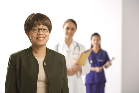 health facility: African American middle-aged woman smiling and looking at viewer with Caucasian mid-adult female doctor and Asian Chinese mid-adult female physicians assistant standing in background.