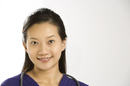 Portrait of Asian Chinese mid-adult female doctor smiling and looking at viewer. photo