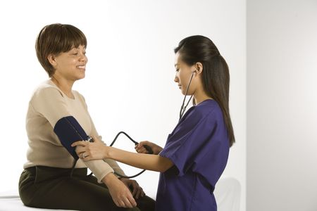 practitioner: Asian Chinese mid-adult female medical practitioner checking blood pressure of African American middle-aged female patient.