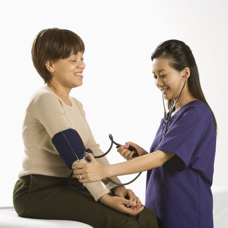 Asian Chinese mid-adult female medical practitioner checking blood pressure of African American middle-aged female patient.