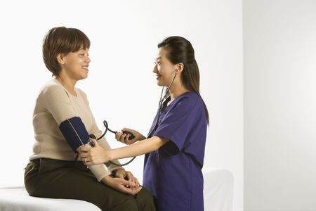 Asian Chinese mid-adult female medical practitioner checking blood pressure of African American middle-aged female patient. photo