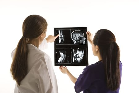 Caucasian and Asian Chinese mid-adult female doctors analyzing x-ray.   photo