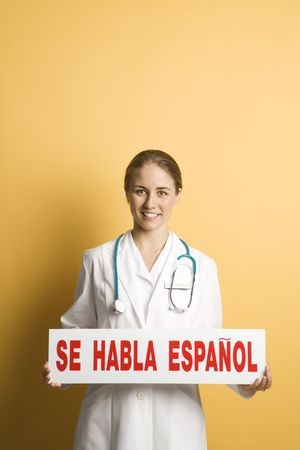Portrait of Caucasian mid-adult female doctor holding up se habla espanol sign against yellow background smiling and looking at viewer. photo