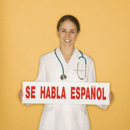 se: Portrait of Caucasian mid-adult female doctor holding up se habla espanol sign against yellow background smiling and looking at viewer. Stock Photo