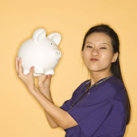 Asian Chinese mid-adult female doctor holding piggy bank against yellow background scrunching nose and looking at viewer. photo