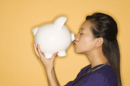 Asian Chinese mid-adult female doctor kissing piggy bank against yellow background. photo