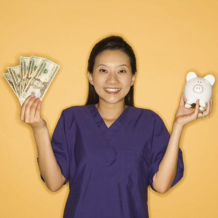 Asian Chinese mid-adult female doctor holding piggy bank in one hand and cash in the other against yellow background smiling and looking at viewer. photo