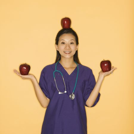 Asian Chinese mid-adult female doctor holding two red apples in hands and balancing one on head against yellow background smiling and looking at viewer. photo