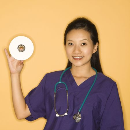 Asian Chinese mid-adult female doctor holding holding up CD against yellow background smiling and looking at viewer. photo