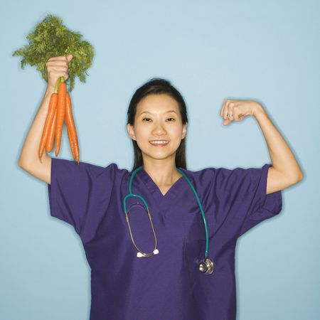Asian Chinese mid-adult female doctor flexing muscle holding up bunch of carrots against blue background smiling and looking at viewer. photo