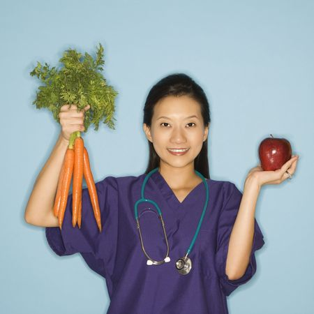 Asian Chinese mid-adult female doctor holding up bunch of carrots with one hand and red apple in other against blue background smiling and looking at viewer. photo