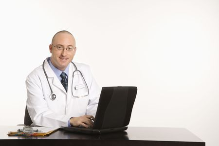 half length posed: Caucasian mid adult male physician sitting at desk with laptop computer.