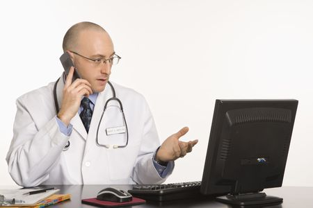 Caucasian mid adult male physician sitting at desk with laptop computer talking on cellphone. photo