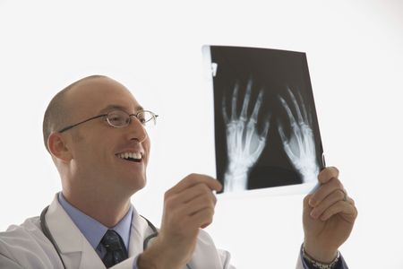 Caucasian mid adult male physician holding up hand xrays. photo