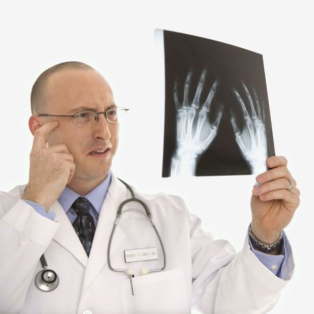 baffled: Caucasian mid adult male physician holding up hand xrays looking perplexed. Stock Photo
