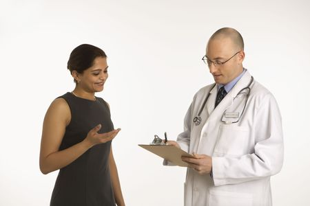 color consultation: Caucasian mid adult male physician talking with Indian woman patient.