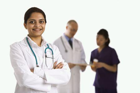 staff medico: Met� di medico indiano della donna delladulto che si leva in piedi con il personale medico nella priorit� bassa.