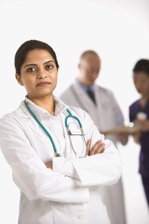 staff medico: Indian met� donna adulta medico in piedi con il personale medico in background.  Archivio Fotografico