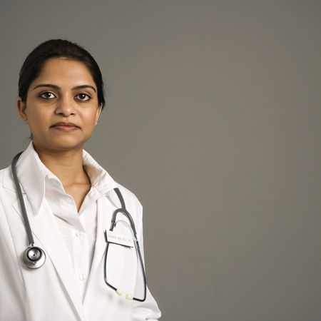 stethescope: Indian woman doctor head and shoulder portrait on gray background.