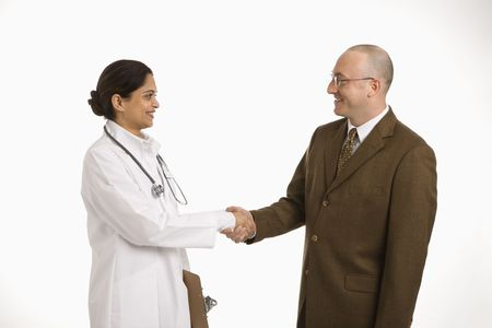 Indian mid adult woman doctor shaking hands with man in business suit.