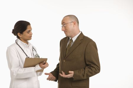 Indian mid adult woman doctor talking with man in business suit. Stock Photo - 2190807
