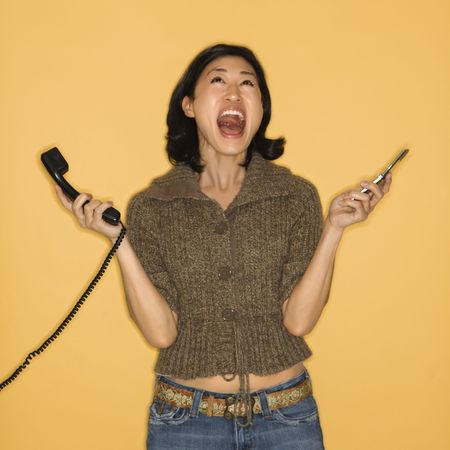 telephone: Pretty mid adult Asian woman holding telephone and cellphone with mouth open. Stock Photo
