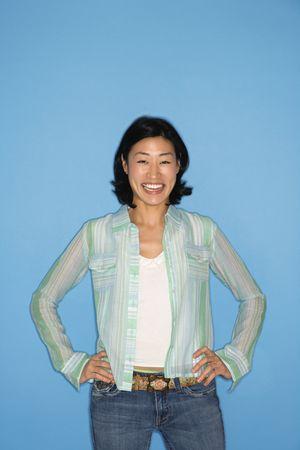 half  length: Half length portrait of pretty Asian mid adult woman  on blue background.
