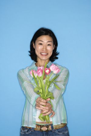 half  length: Half length portrait of pretty Asian mid adult woman holding flowers on blue background.