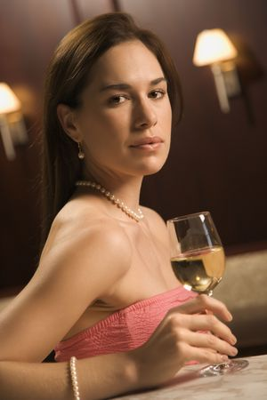 half length posed: Mid adult Caucasian woman sitting at bar with glass of white wine looking at viewer. Stock Photo