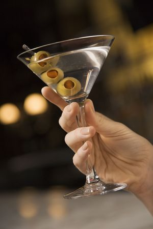 mid adult female: Mid adult female Caucasian hand holding a martini with three olives.