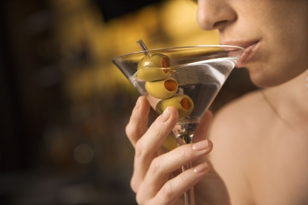 alcoholic drink: Close up of mid adult Caucasian woman drinking a martini with three olives.