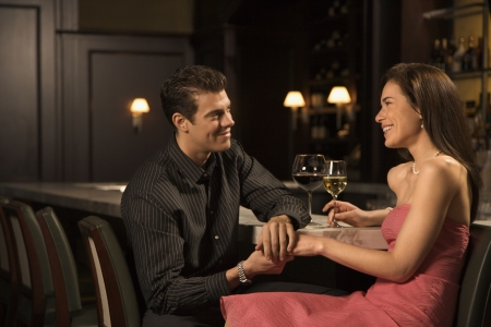 image date: Mid adult Caucasian couple at bar holding hands and smiling.