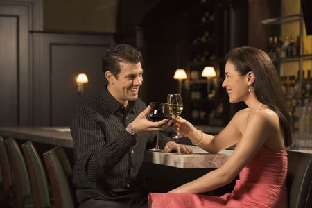 Mid adult Caucasian couple at bar toasting wine glasses and smiling. photo