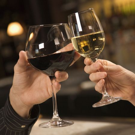 casal: Mid adult Caucasian male and female hands toasting wine glasses.