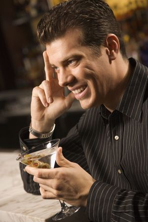 half length posed: Side view of mid adult Caucasian man holding martini with hand to head smiling.