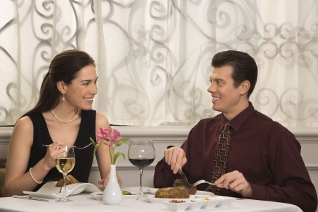Mid adult Caucasian couple smiling eating in restaurant. photo