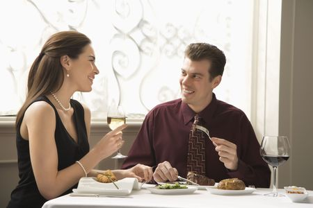 Mid adult Caucasian couple dining in restaurant and smiling. photo